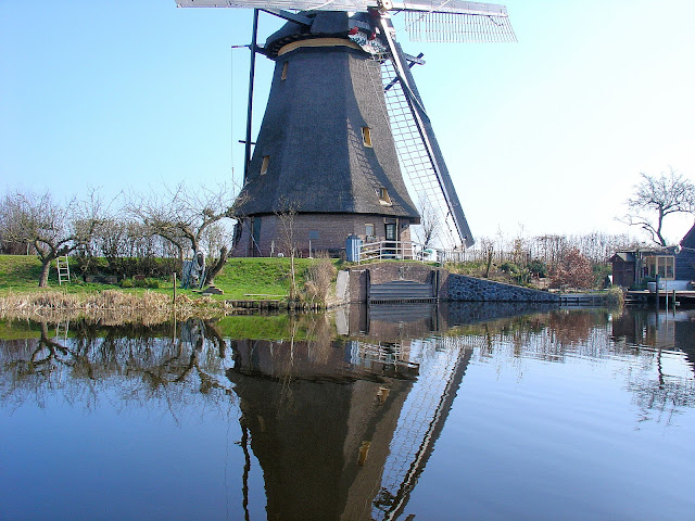 Reflections in Kinderdijk Windmill Complex in The Netherlands. All content property of EuroTravelogue™. Unauthorized use is prohibited.