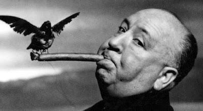 Alfred Hitchcock com um charuto em sua boca e um pássaro em cima