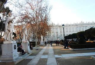La estatuas forman hilera, flanqueando bancos de piedra, al fondo el Palacio Real y en medio los jardines.