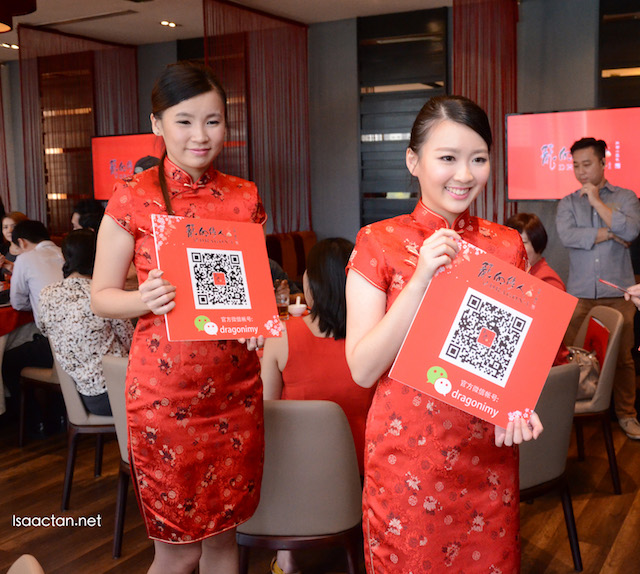 Pretty ladies holding on to the QR Code to add and follow dragonimy in your WeChat