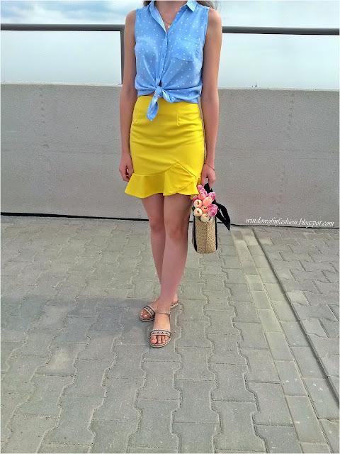 Niebieska koszula w kropki, żółta spódnica z flabanką, beżowe sandały, tulipany