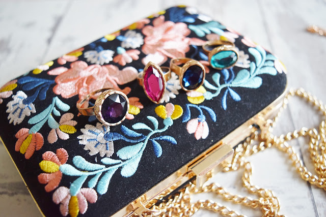 colourful clutch bag and rings