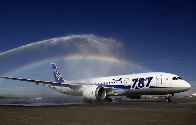 A Boeing 787 taxis under a rainbow created by fire trucks at Seattle-Tacoma International Airport, in Seattle.