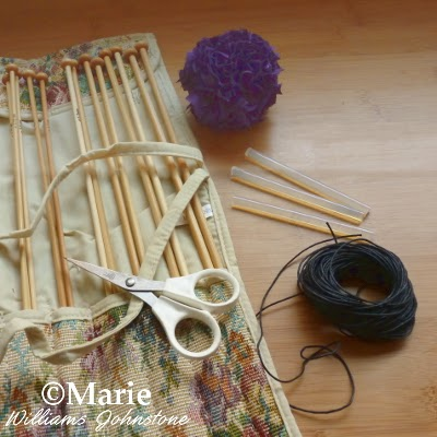 Fabric pom pom, wooden knitting needles, black cord, glue sticks, scissors