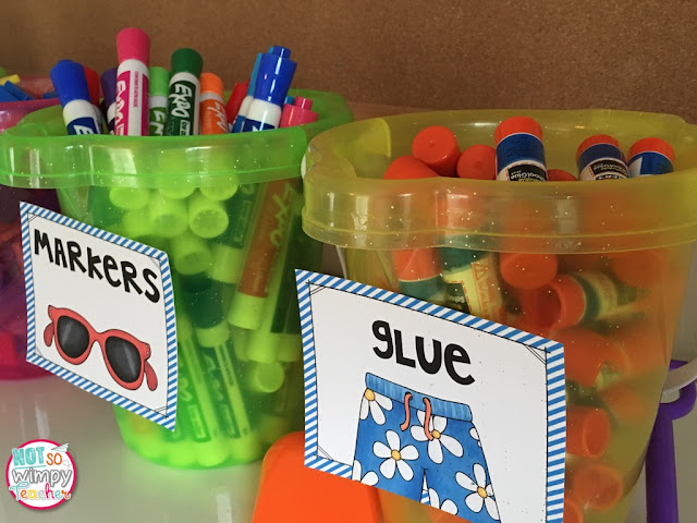 "Not So Wimpy Teacher incorporated beachy touches with labels for classroom supplies. Here, there are two buckets of materials with beach-themed labels: one with ""markers"" and a pair of sunglasses, and the other with ""glue"" and a pair of bright swim shorts"