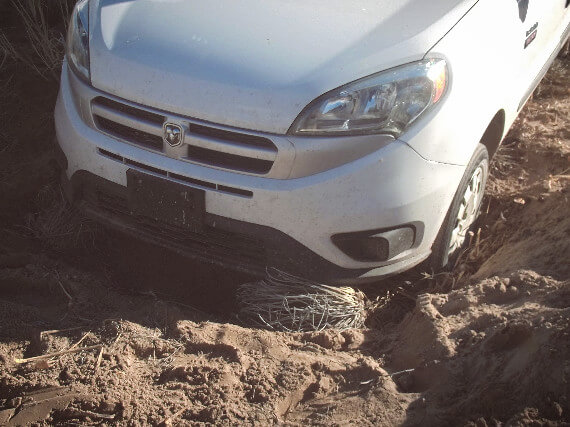 Vanholio's Promaster City van front end wheels dug into a New Mexico sand hole at Hunts Hole  – vanholio.com