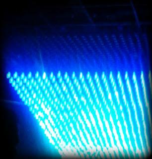Színes digitális fotó egy koncert fénytechnikájáról, az állványzatról reflektorok, effekt lámpák, lézerek világítják meg a színpadot és a nézőket.