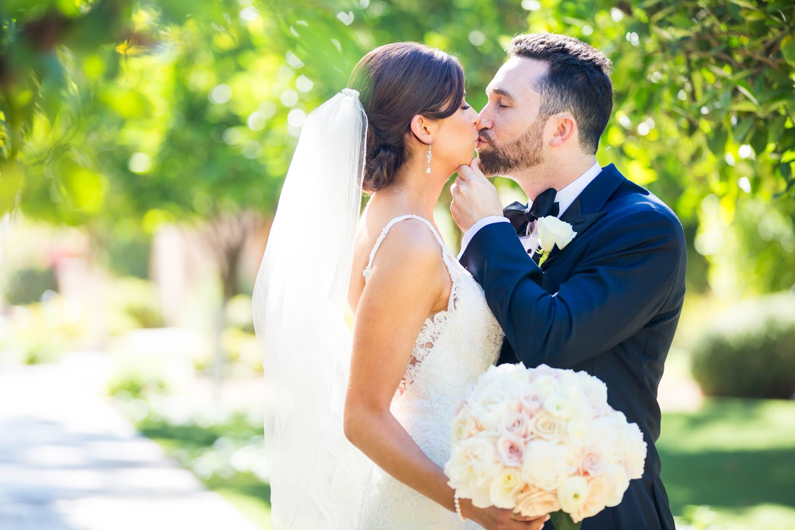 classic romantic bride with white and blush roses wedding bouquet kissing groom in navy suit at Omni Montelucia