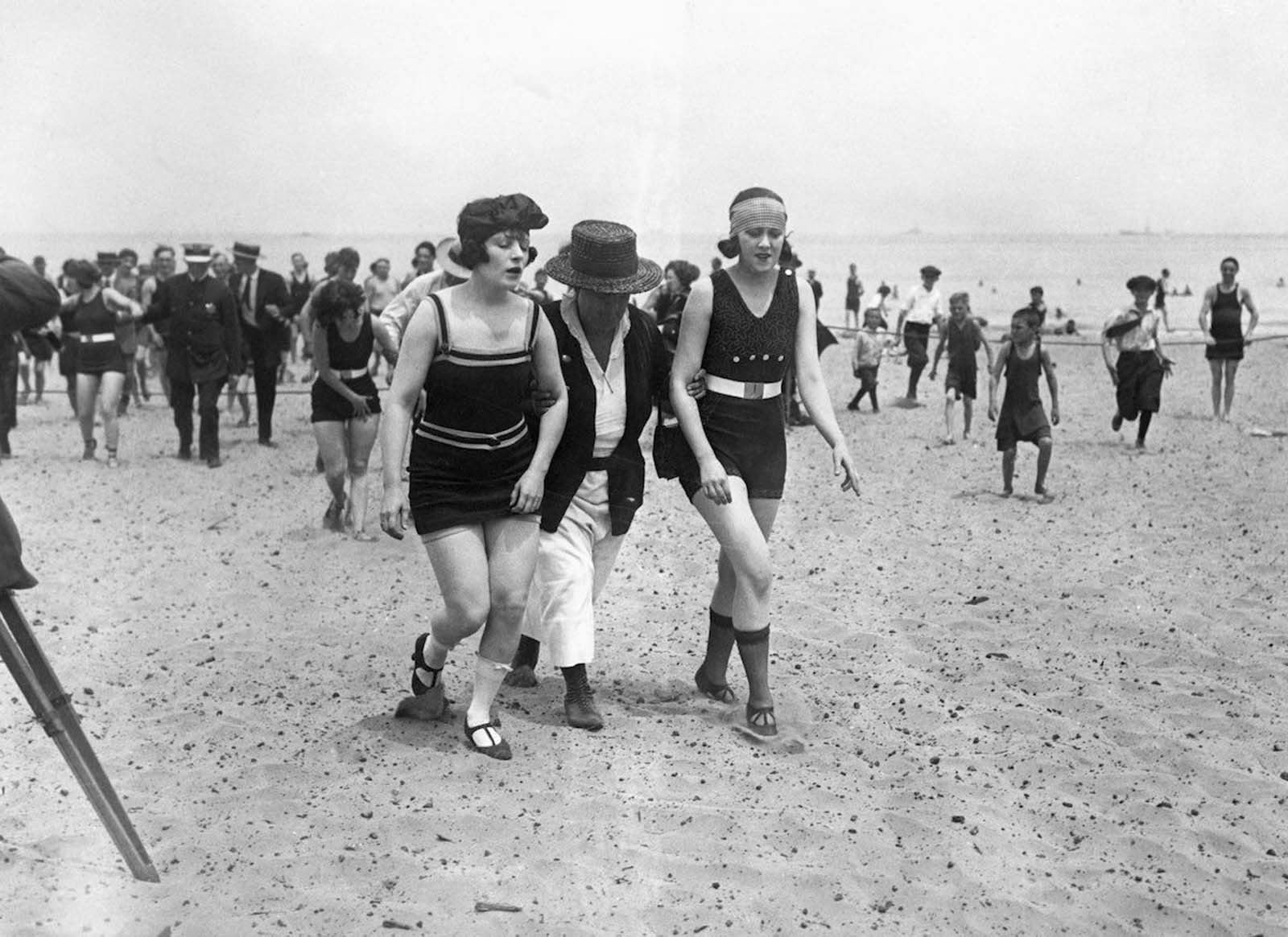 Two bathers being escorted off the beach by a police woman. Chicago, 1922.