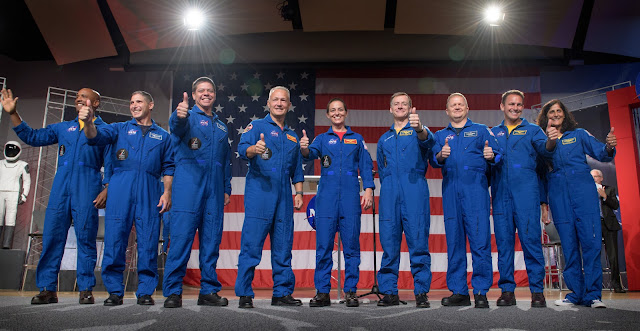 The first U.S. astronauts who will fly on American-made, commercial spacecraft to and from the International Space Station, wave after being announced, Friday, Aug. 3, 2018 at NASA's Johnson Space Center in Houston, Texas. The astronauts are, from left to right: Victor Glover, Mike Hopkins, Bob Behnken, Doug Hurley, Nicole Aunapu Mann, Chris Ferguson, Eric Boe, Josh Cassada, and Suni Williams. The agency assigned the nine astronauts to crew the first flight tests and missions of the Boeing CST-100 Starliner and SpaceX Crew Dragon. Photo Credit: (NASA/Bill Ingalls)