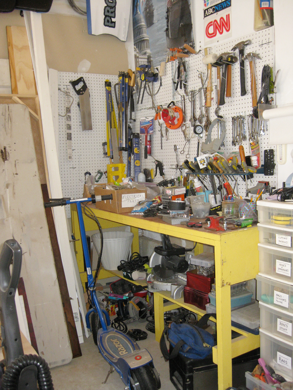 disorganized garage with pegboard and yellow working bench