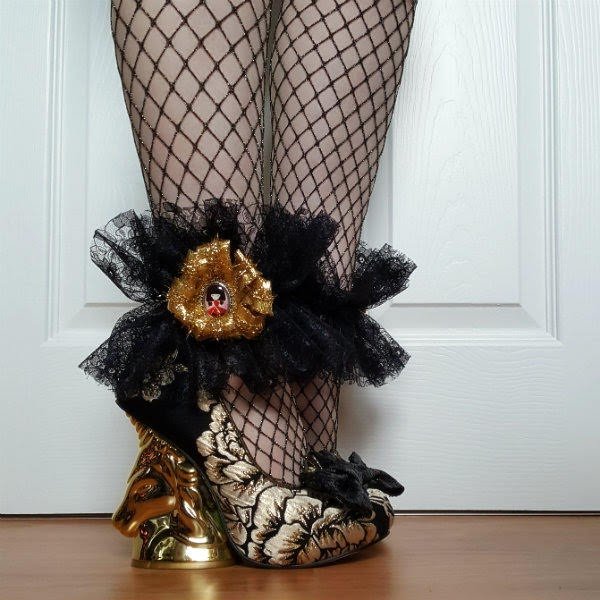 gold unicorn heeled shoes worn with fishnet tights and black lace ankle cuff