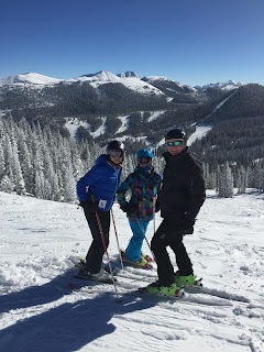 A family of 3 skiing on a sunny day with snow covered trees.
