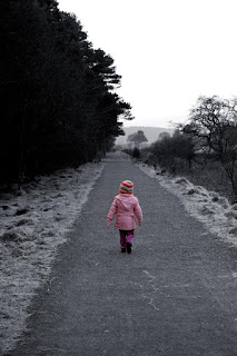 Photo of a small girl walking down a deserted road alone