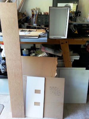 Four offcuts of MDF, in various sizes, leaning against a workbench in a house.
