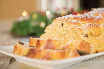 Pan dulce trenzado sobre una bandeja, con dos porciones cortadas.