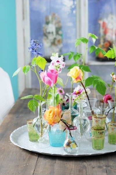 Berbagai jenis botol beraneka warna menjadi vas beragam jenis bunga.