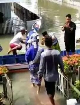 Sepangan pengantin yang diangkut naik sampan.