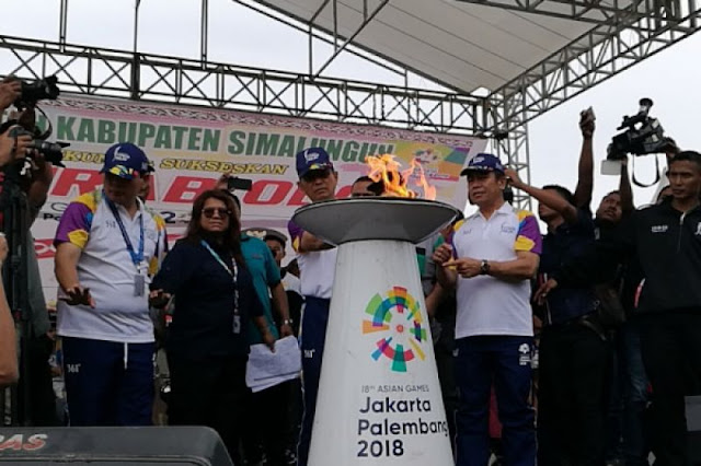 Bupati Simalungun JR Saragih menyulutkan api Asian Games 2018 dari obor ke mini cauldron di Pantai Bebas, Danau Toba, Sumatera Utara