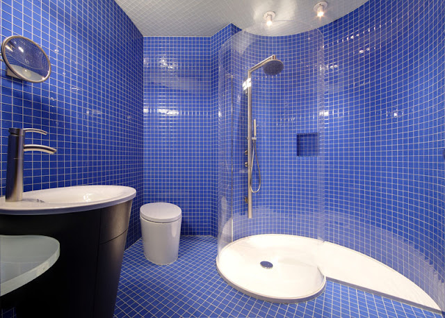 blue tiled bath with glass tube shower