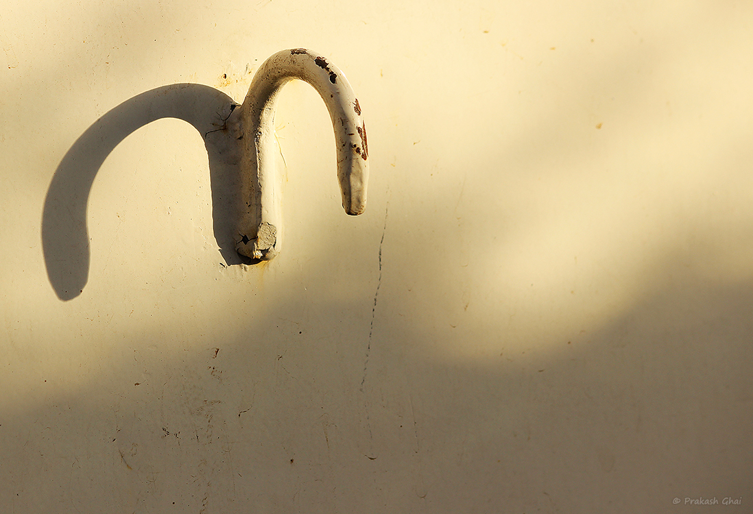 A Minimalist Photo of the Shadow of a metal hook on a cargo truck.