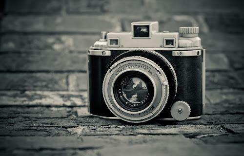 Foto de uma antiga câmera Kodak Supermatic sobre o chão