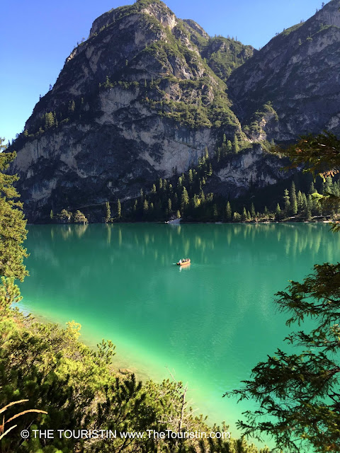 Emerald water of Lago di Braies with the mountains of the UNESCO listed Prags Dolomites in the background