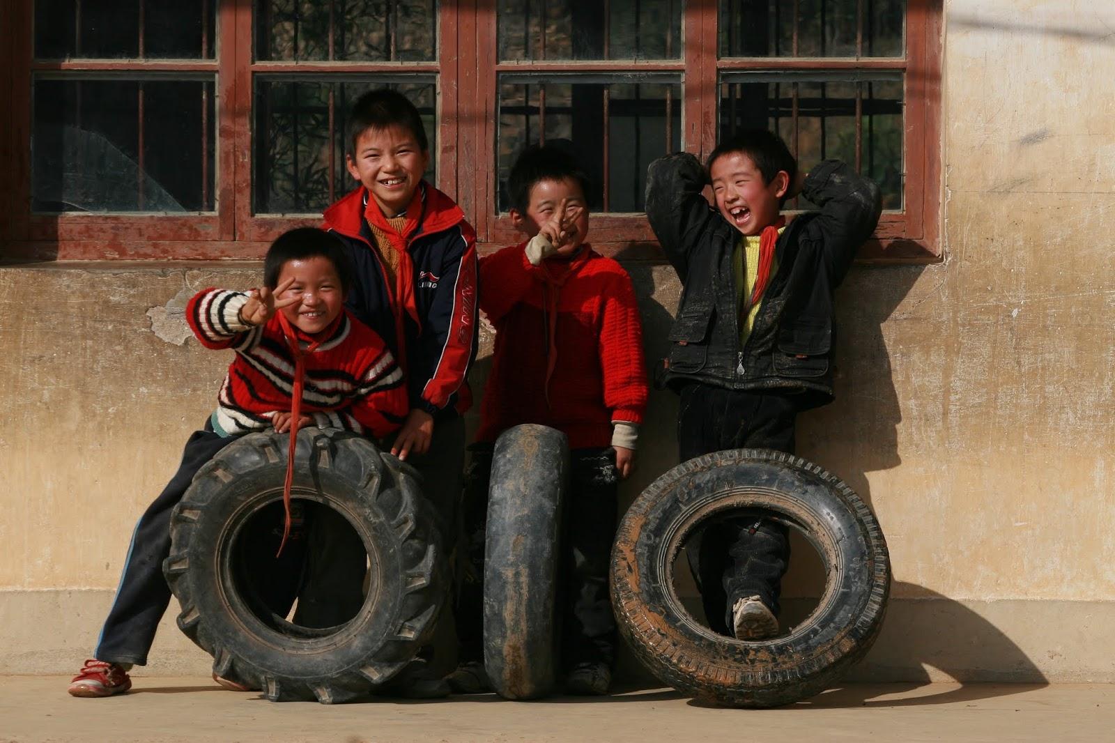 Quatro meninos chineses sorridentes posam para foto encostados em uma parede ilustra este post sobre o Shijing, o Livro das Canções.
