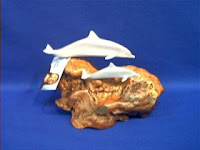 small dolphin figurine pair on burled wood by john perry