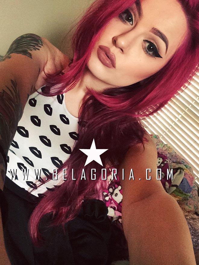 Vemos a una preciosa mujer de pelo rojo con tatuajes delicados