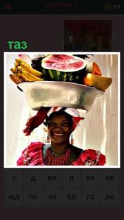 женщина на голове несет таз с фруктами