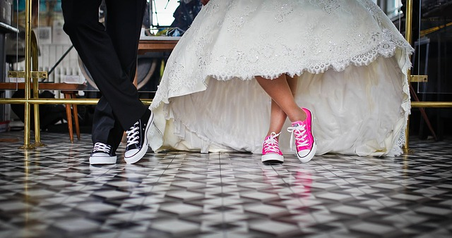 In preparation for marriage, husband and wife on sneakers cross legs to take a photo shoot