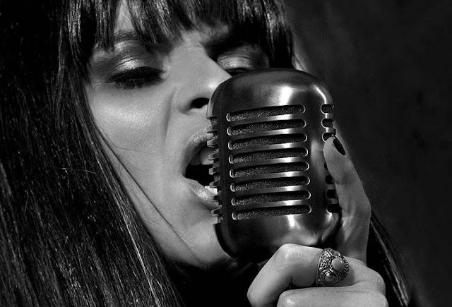 O rosto da vocalista Juh Leidl em destaque, com o microfone na mão