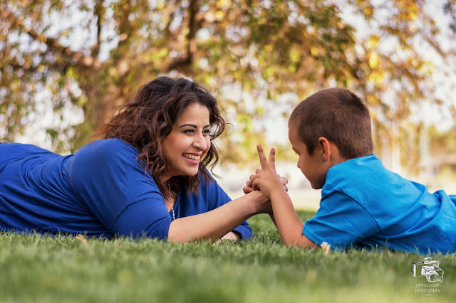 a brother and sister arm wrestle in the grass at a park for their portrait session
