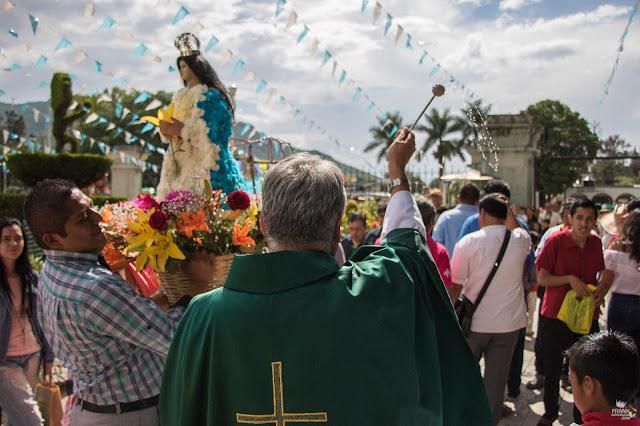 Sacerdote bendiciendo canastas florales