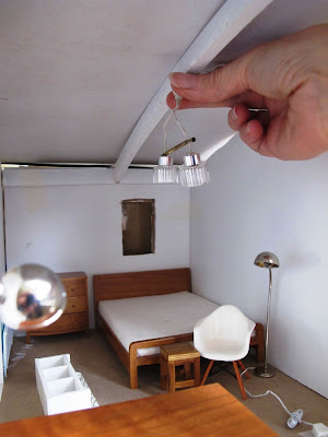 Woman holding a miniature light up to the ceiling of a dry-fitted modern miniature doll's house shed.