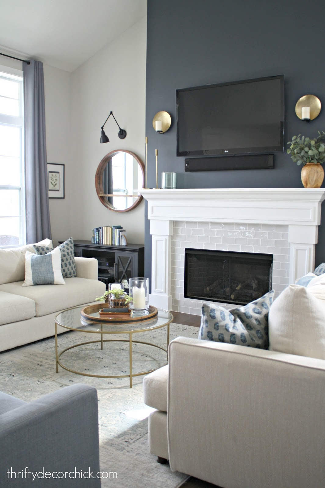 Dark wall, white fireplace surround, gray tile