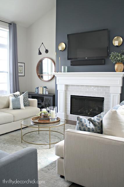 Dark wall, white fireplace surround, gray tile