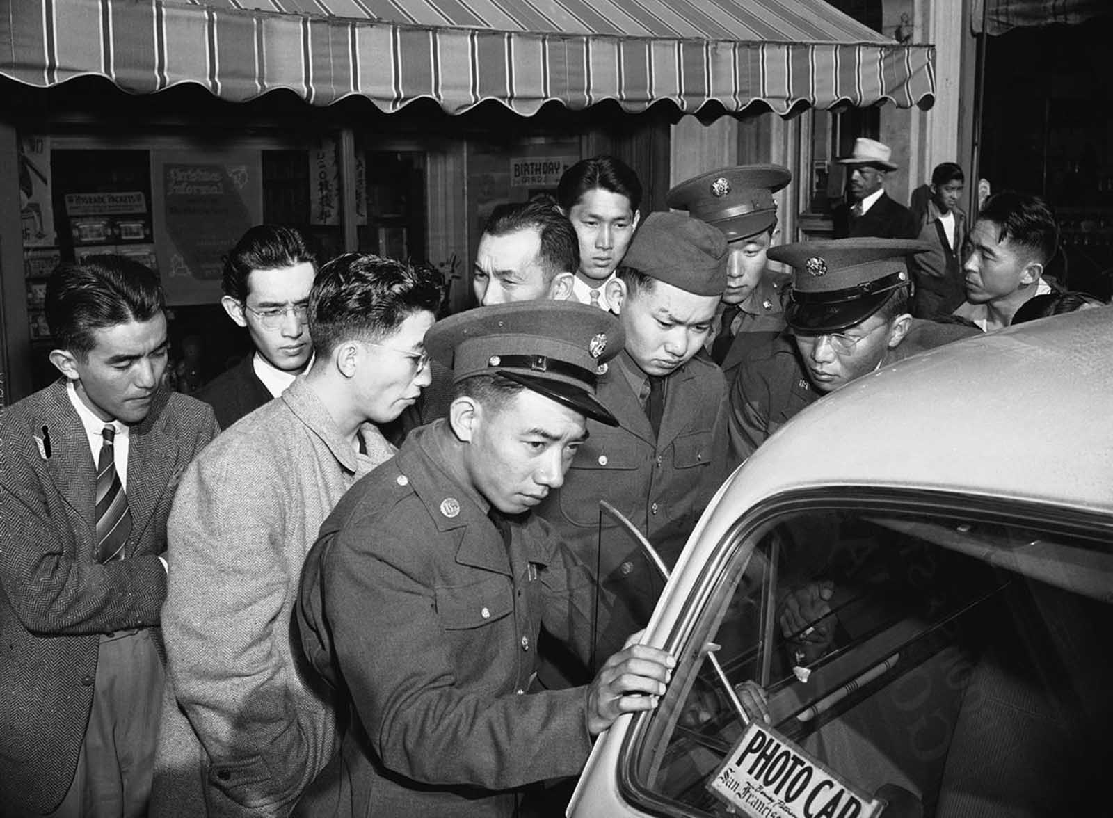 Young Japanese Americans, including several Army selectees, gather around a reporter's car in the Japanese section of San Francisco, on December 8, 1941