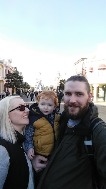 Mum and Dad with a toddler on Main Street at Disneyland Paris with castle in the background