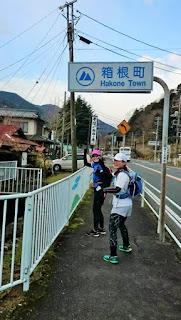 箱根町の標識を通過するランナー二人