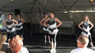 Group of teen girls standing with hands on their hips wearing black and white dance outfits