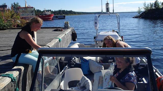 Aurinko paistaa kun kolme henkeä pakkaa venettä laiturilla