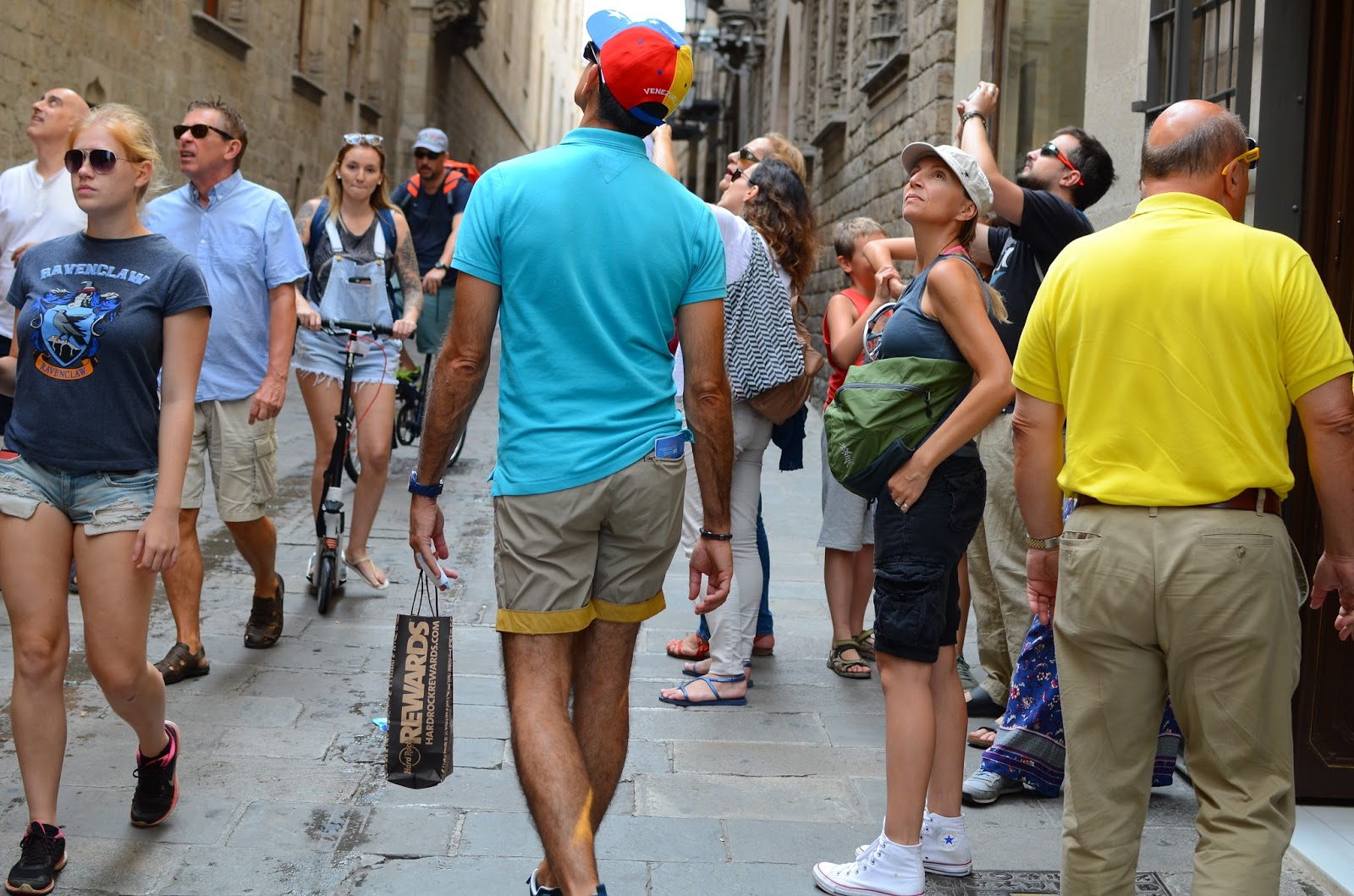 Tourists look up for best image subject at Carrer del Bisbe, Barcelona