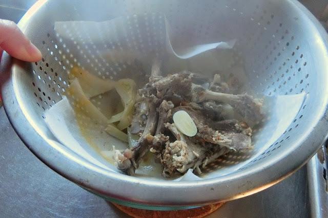 煮込んだスープをざるで漉す
