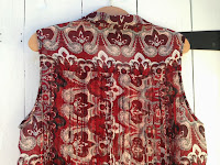 The back of the red blouse which has fringe detailing just below the shoulders