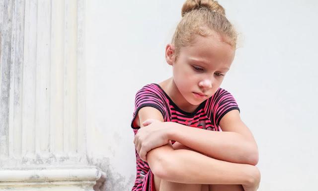 Menina criança cabisbaixa, triste, baixa autoestima, efeito elogio inflado