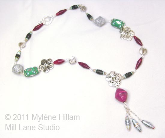 Handmade burgundy and fuchsia paper beads combined with silver flower connectors and aquamarine Kashmiri-style beads in a necklace