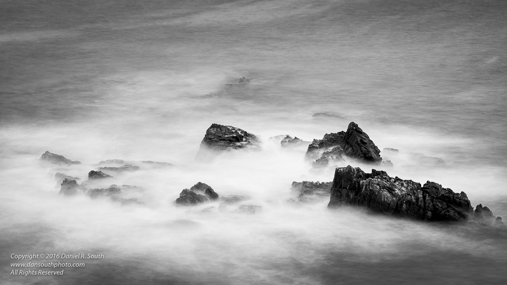 a photo in black and white of ocean waves passing over rocks