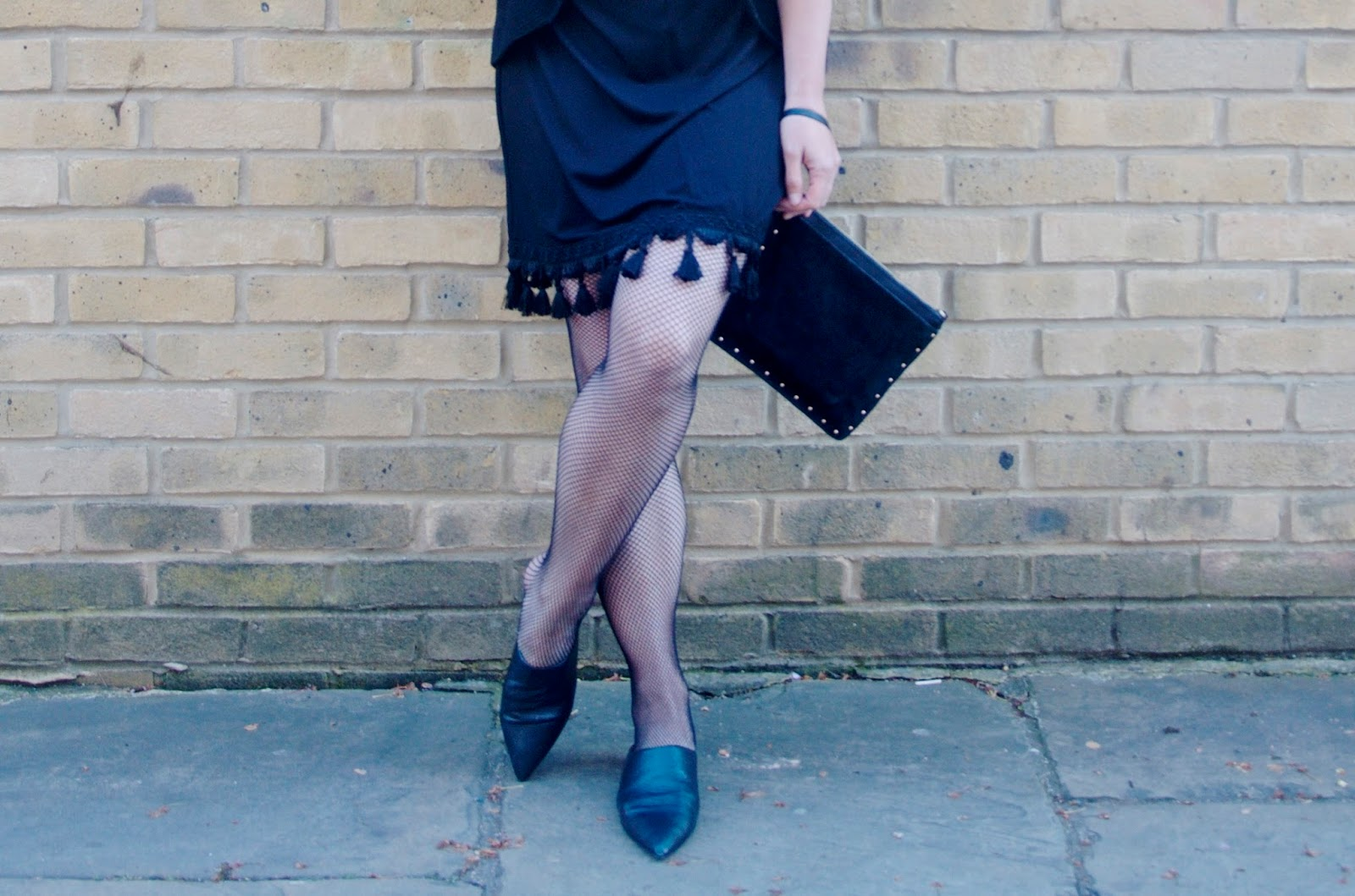 studded black suede clutch, fishnets and black tassel trim dress